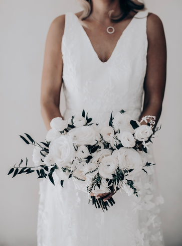 bride holding bouquet of white wedding flowers