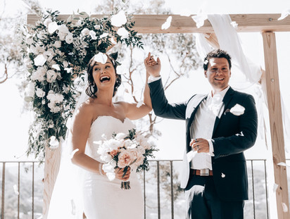bride and groom under wedding arch decorated with flowers