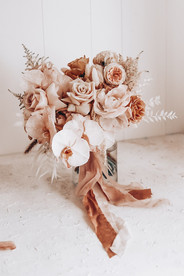bridal bouquet featuring roses and orchids in rust tones