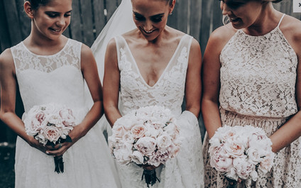 bride and bridesmaids holding bouquets of roses and peonies