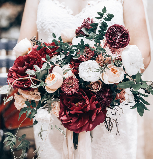 bridal bouquet of roses peonies and berries in butgundy and apricot tones