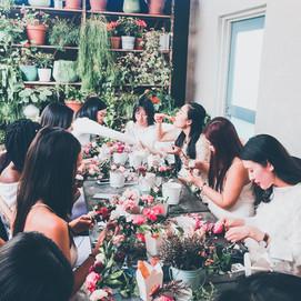 ladies sitting at table making flower crowns