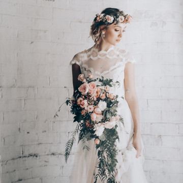 bride wearing flower crown and holding trailing bouquet