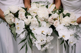 bride and bridesmaids holding white bouquet of orchids and peonies