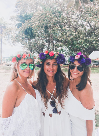 girls in white dresses wearing flower crowns