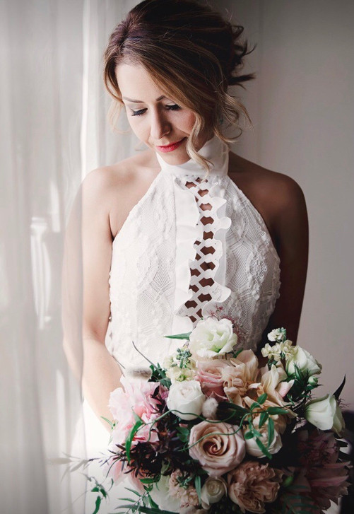 bride standing by window holding bouquet of flowers