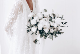 ady wearing white holding bridal bouquet of white flowers