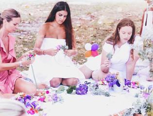ladies sitting on picnic blanket making flower crowns