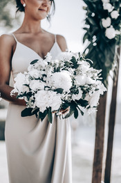 bridesmaid holding bouquet of white tropical flowers