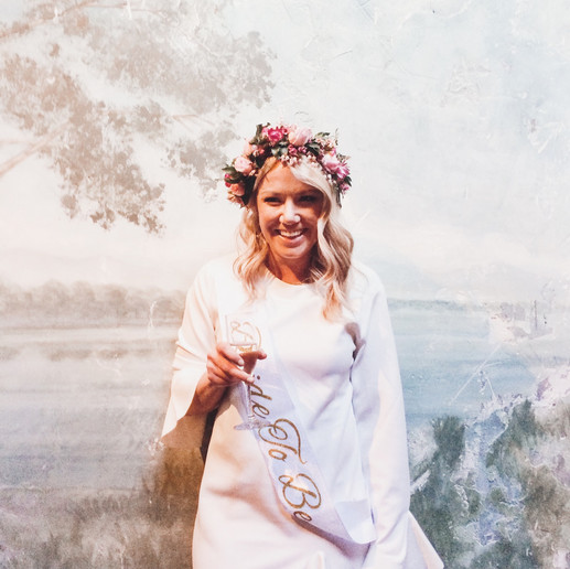hens party bride wearing flower crown holding champagne