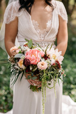 bride holding wedding bouquet of peonies and natives