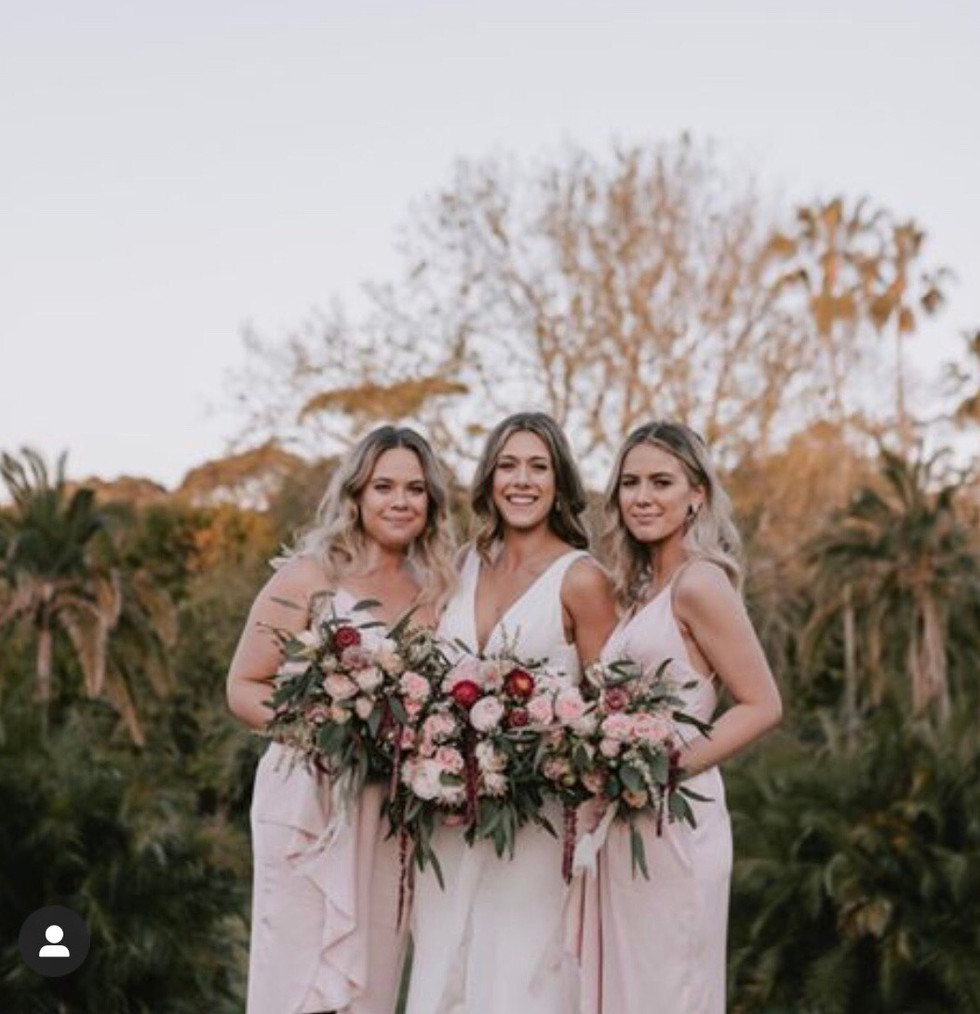 bride and bridesmaids holding bouquets of native wedding flowers