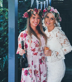 bride and friend wearing flower crown holding champagne