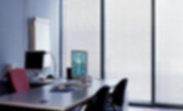 Oficina con escritorio y cortinas plateadas