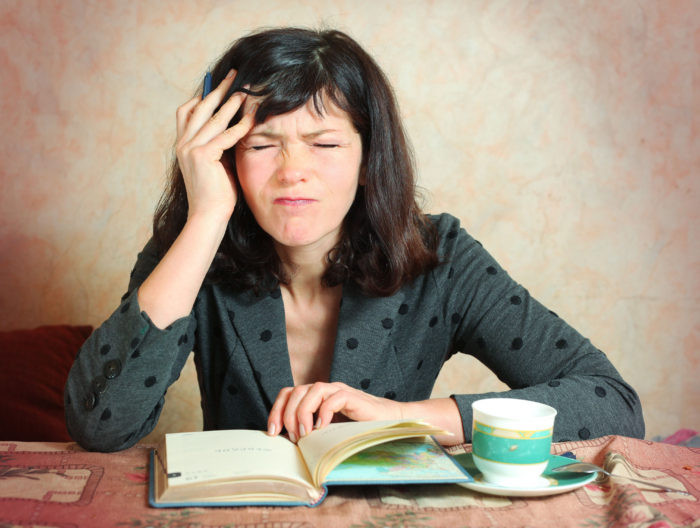 business woman with organizer and cup of coffee having severe headache