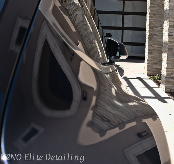 Mirror Paint Correction Shot of Silver Tesla Model 3