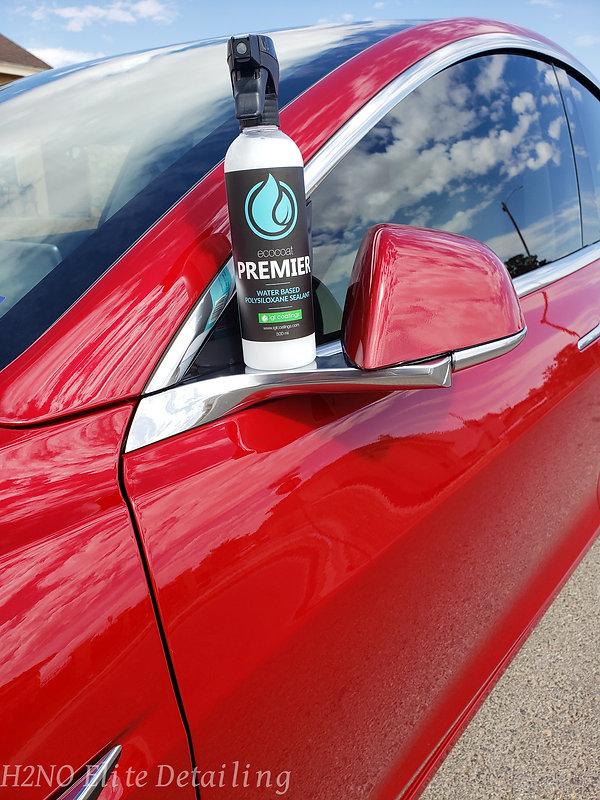 Spray ceramic coating bottle on red Tesla Model 3 mirror