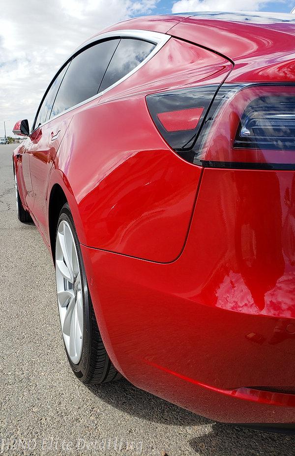 Rear driver corner view of red Tesla Model 3 detailing in El Paso TX