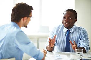 deux hommes discutent à un bureau