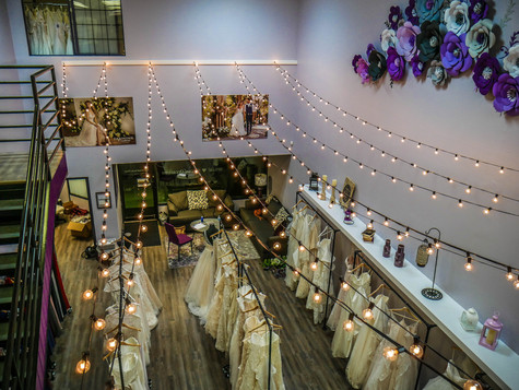 View of our Colorado Springs Boutique from the private loft area. Fair lights and wedding dresses. A personal experience with a wedding dress consultant and advisor.