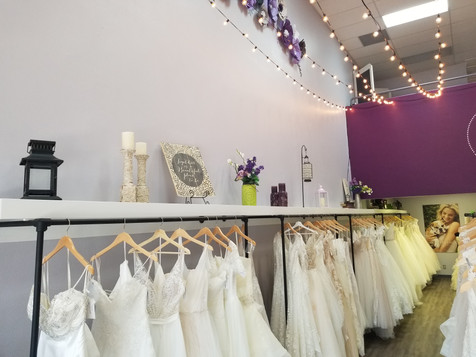 A line wedding dresses and ballgown wedding dresses hanging on the rack in our store. Wedding decor and fairy lights.