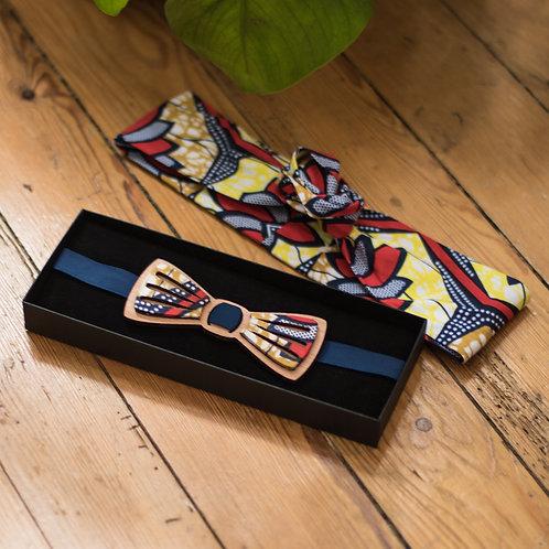 un noeud papillon en bois et wax et un headband en tissu wax assorti sont posés sur un parquet en bois ancien