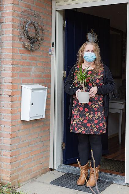 Vrouw met plant en mondkapje