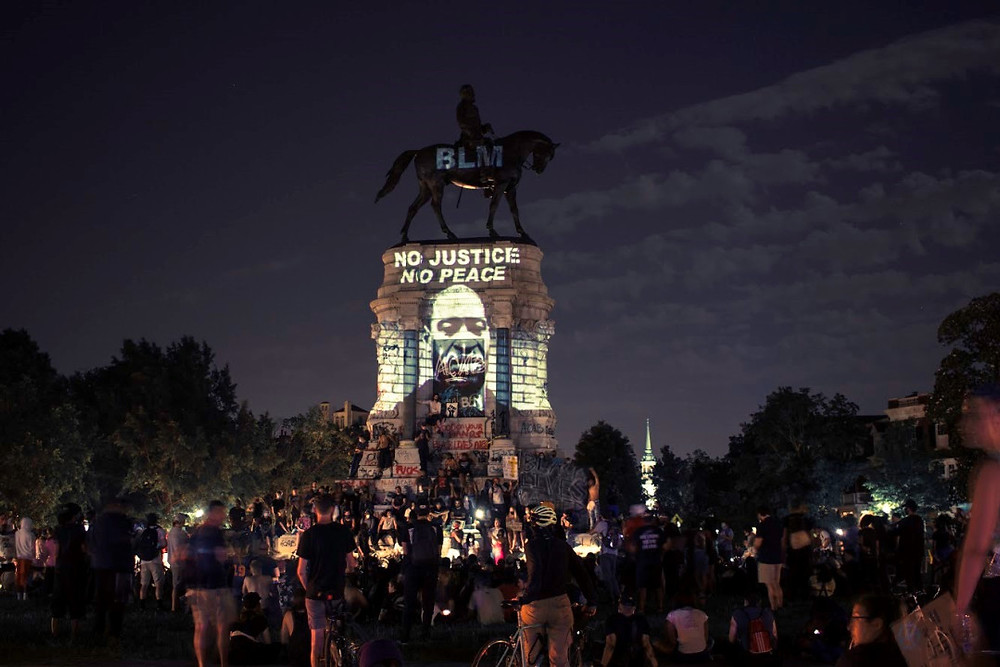 Richmond's Robert E. Lee statue with protestors and projections.