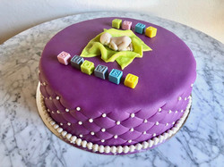 Lila tårta m. kuber & bebis
