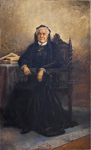 Retrato de Luza Bruce, vestida de preto, sentada numa cadeira ao lado de uma mesa com livros.
