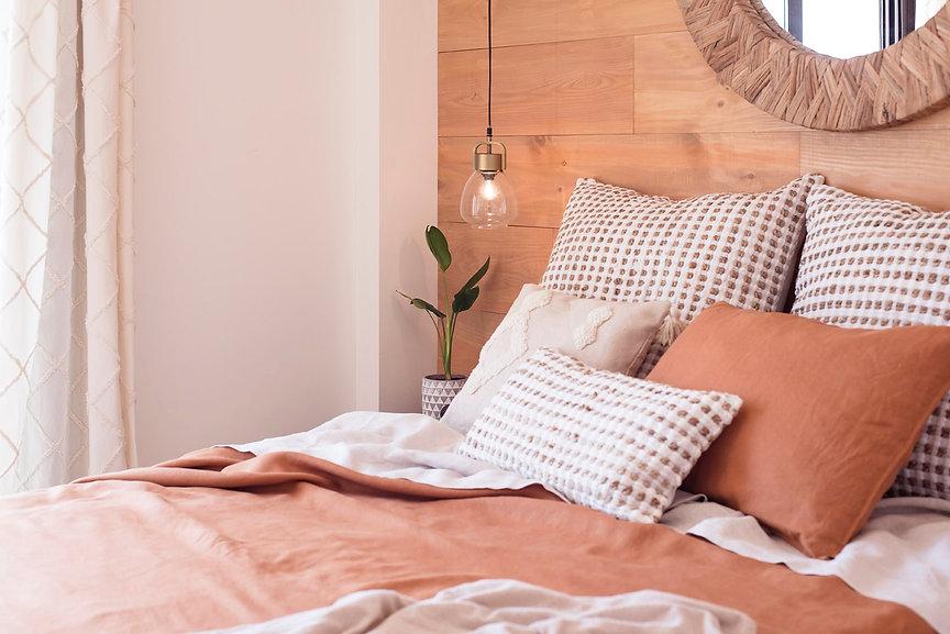 Dormitorio diseñado y decorado por el interiorista Noogar, en Caleta de Fuste, Fuerteventura. Habitación de estilo natural con pared forrada de madera y colores naturales, con un toque de color tierra.
