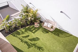 Outdoor space designed by Noogar interior designer in Fuerteventura. Garden with artificial grass and Brazilian style garden.