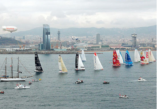 Barcos de vela navegando en la costa de Barcelona, skyline Barcelona con el mar. Nuves grises