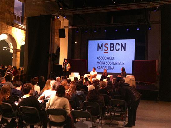 Sala de desfiles en el museo Santa Monica de Barcelona, con pantalla donde se proyecta el logo de MSBCN y de la Asociació Moda Sostenible Barcelona, ponente hablando de pié y otros 3 sentados en el escenario. Público sentado en la sala.