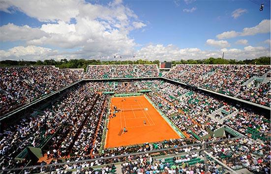 vista aérea de la pista central de Roland Garros, edición 2014. gradas llenas de gente, dos jugadores en la pista de juego. Evento deportivo sostenible, implementación de la norma ISO 20121