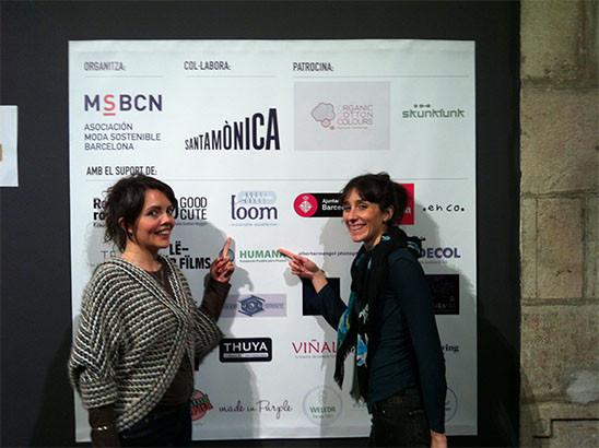 dues noies, Maite Escribano i Sol Magaroles, treballadores de l'empresa Loom senyalen el logo de loom, que està al costat del logo de l'Ajuntament de Barcelona, en el vinil dels logos. loom dóna suport al festival.