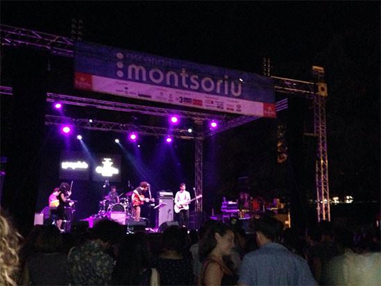 concierto del festival Pop Arb Arbúcies, conjunto tocando en el escenario del festival por la noche. gente bailando y bebiendo. Luces violeta en el escenario