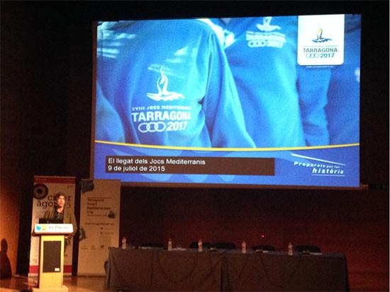 Imagen proyectada de los juegos de la Meditarrania de Tarragona 2017, dentro de laas jornadas de Ciberágora. Ponente hablando en un atril en el escenario. Mesa de ponentes al lado. Públiico sentado delante.