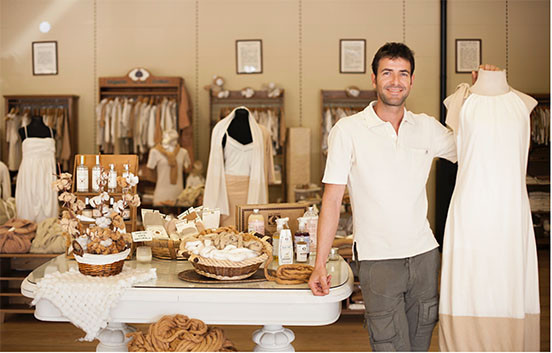 Santi Mallorquí en su tienda de Organic Cotton Colours, Mesa con productos de algodón orgánico. Al fondo, maniquís con vestidos de algodón, y estanterías con prendas de algodón. Color blanco y beige.