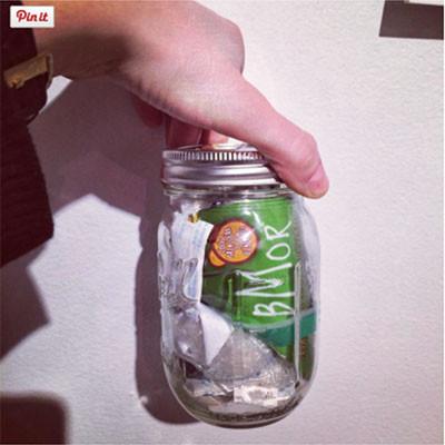 mano de Lauren Singer con un pote de cristal donde hay los residuos y basura que ha generado en 4 meses.