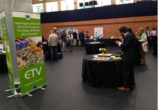 Enterada a la sala de conferencias. Letrero verde de ETV con información, mesas redondas preparadas con el catering con productos de proximidad. Gente de pié hablando y comiendo.