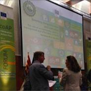 detalle de una sala de conferencias, con pantalla de proyección don diapositiva de la ETV. Un hombre y una mujer hablando entre ellos, bandera catalana, roll up del Forum ETV