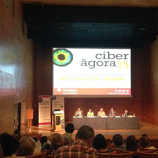 Sala de congresos con pantalla proyección, mesa con ponentes hablando y público sentado. Jornadas de Ciberagora, en Tarragona,