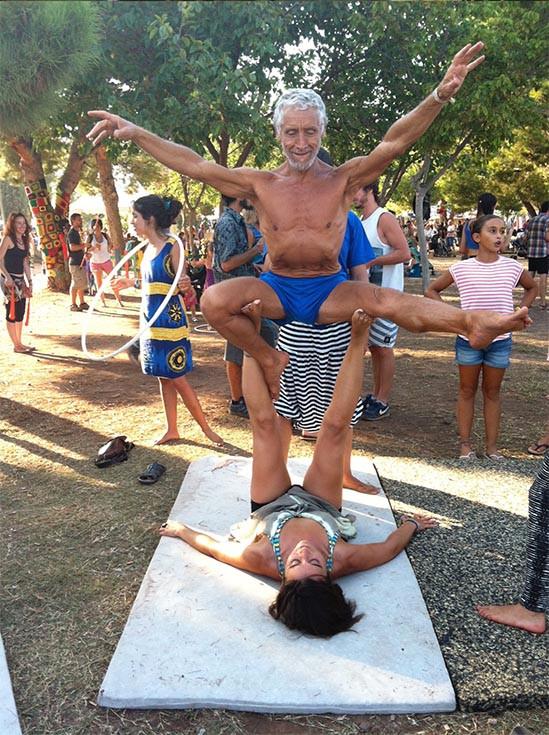 dos personas realizando una postura de yoga. Niña con julahoob, parque con mucha gente divirtiéndose, haciendo actividades y hablando