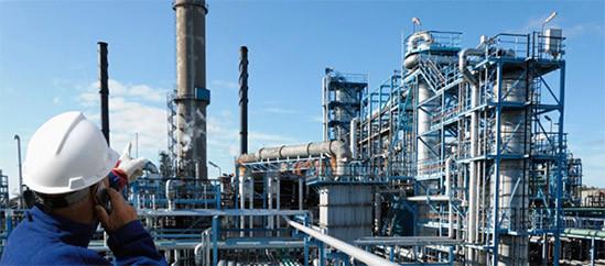 una fábrica industrial en funcionamiento que tiene que implementar la ISO 14001. Trabajador con casco de obra protector, habla por teléfono mientras señala a una de la torres de ventilación.