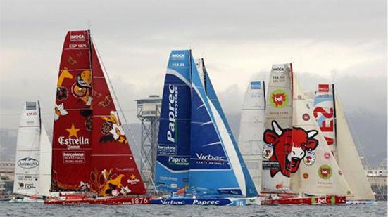 Barcos veleros de la Barcelona World Race. Velas patrocinadas por Estrella Damm, Paprec, Leche Asturiana, La Vaca que ríe. Veleros en carrera en el puerto de Barcelona