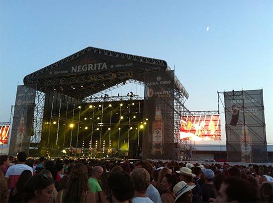 escenario de música con grupo musical tocando. focos encendidos. gente bailando de pié. pantallas laterales.