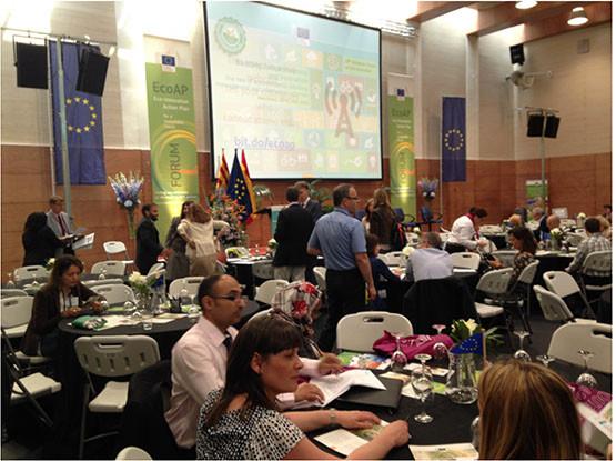 Sala de conferencias del Congreso ETV, Verificación de Tecnologías Ambientales. Sala con un a pantalla con proyección de diapositiva, varias mesas redondas con gente sentada escuchando y anotando en sus ipads. Gente de pie hablando entre ella.