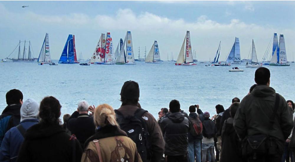 Público de pié viendo la competición de la Barcelona World Race en el puerto de Barcelona. Día gris. Veleros en el mar