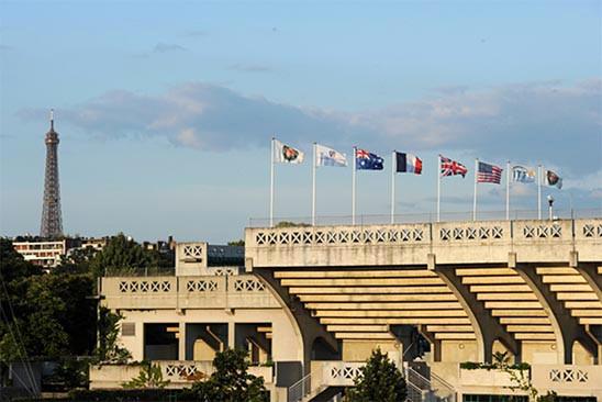 estadio de tenis de Roland Garros, torneo de tenis. Banderas de diferentes paises, sia soleado, por la tarde. Torre Eifeld al fondo. Aplicación de la norma ISO 20121